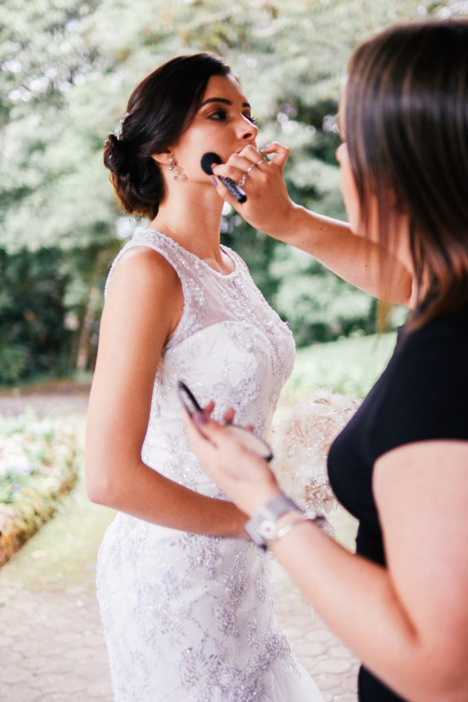 girl in white dress getting makeup done