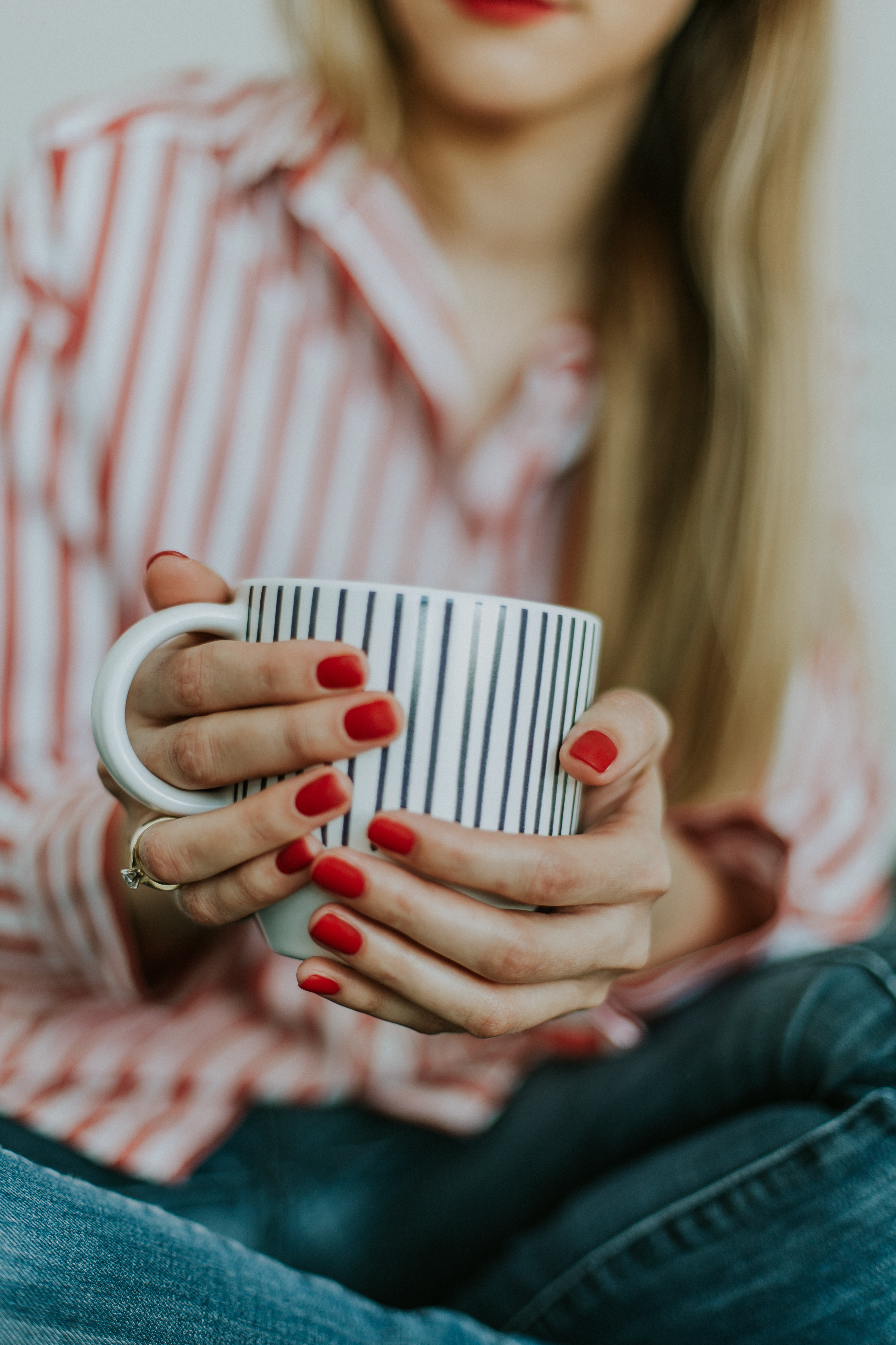 Girl with red nails holding cup