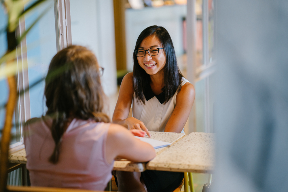Two women talking and smiling across a table