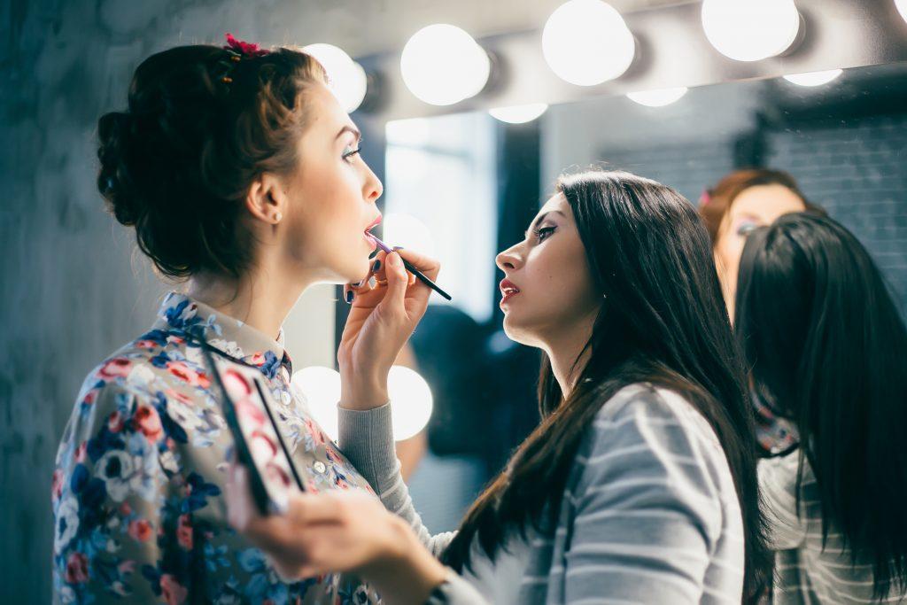girl applying lip liner on another girl